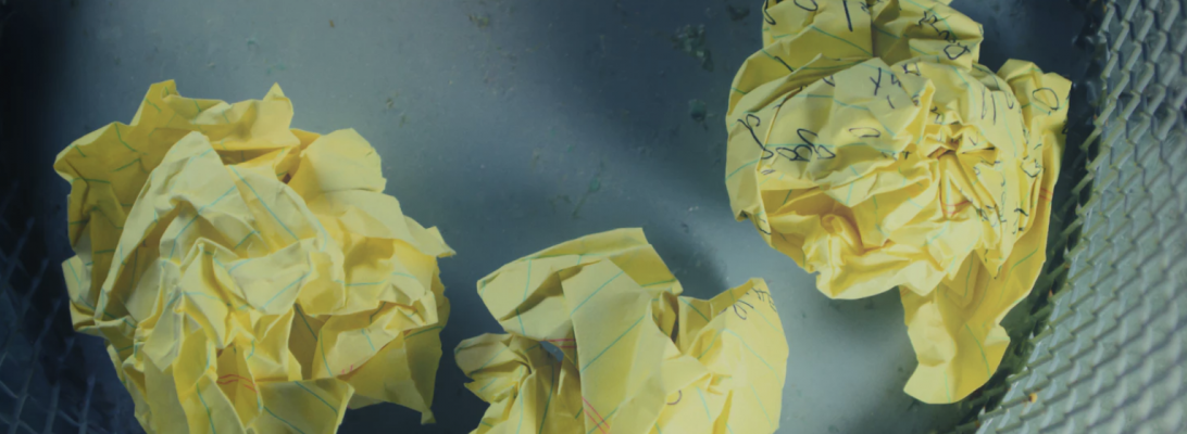 Picture of three crumbled up balls of yellow paper in a rubbish bin